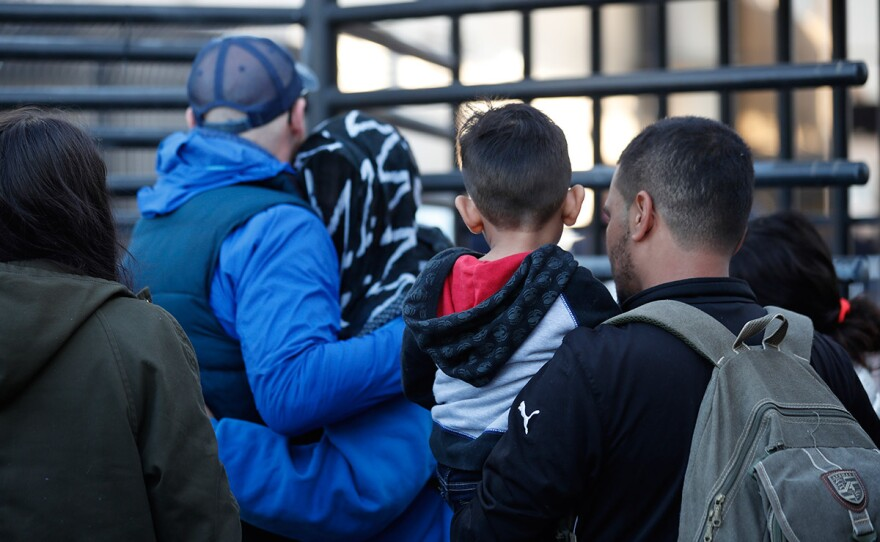 Honduran asylum seekers enter the U.S. at San Diego's Otay Mesa port of entry, as seen from Tijuana, Mexico, Tuesday, Dec. 18, 2018.