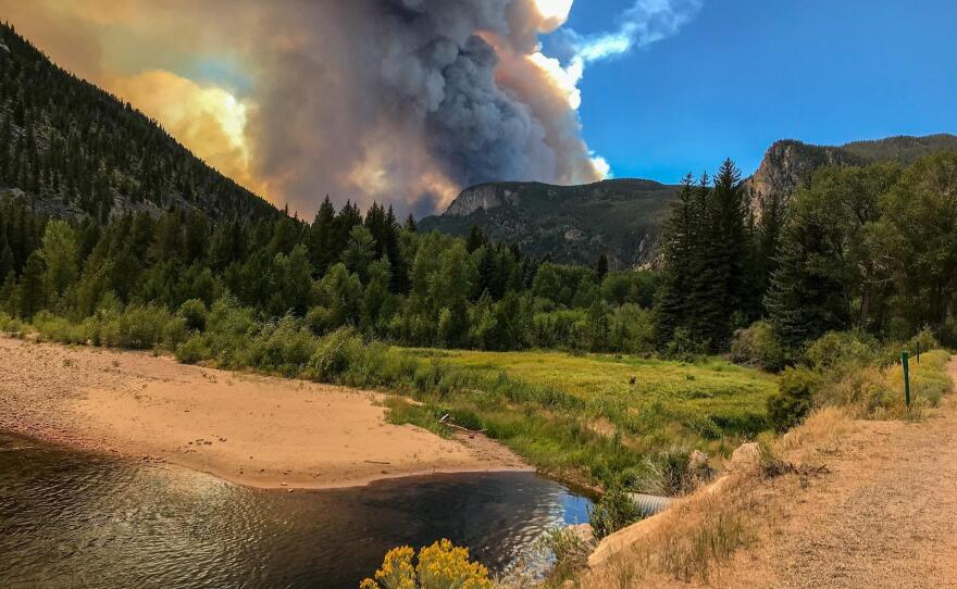 An undated photo depicting large smoke clouds coming from the mountains behind the Poudre River watershed. Between the High Park and Cameron Peak Fires, a broad reach of the Poudre River's watershed has burned within the last decade