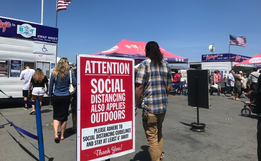 A sign outside the entrance of Kobey's Swap Meet at the Sports Arena encourages guests to social distance due to the COVID-19 pandemic. April 10, 2021.