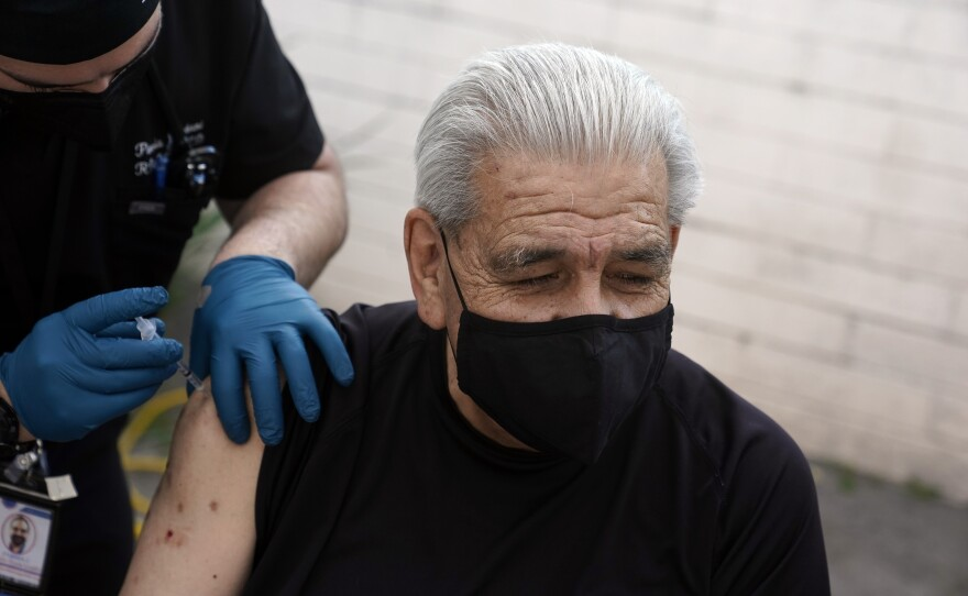 Edward Muro gets a shot of Pfizer's COVID-19 vaccine at Families Together of Orange County Community Health Center, Friday, Feb. 26, 2021, in Tustin, Calif.