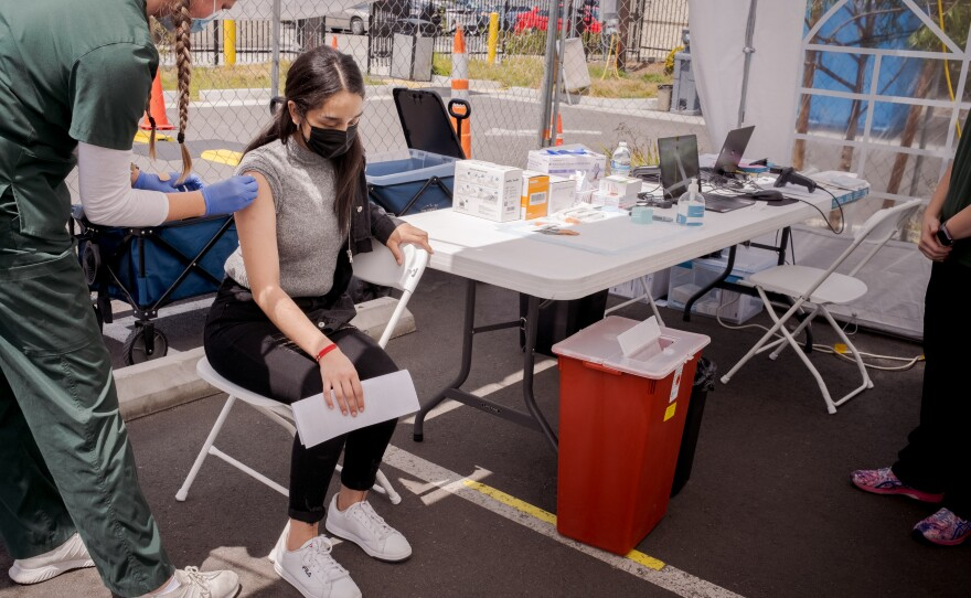 A girls receives the Pfizer COVID-19 vaccine at the Family Health Centers of San Diego in Barrio Logan, May 13, 2021.