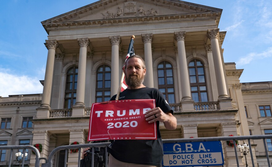 A supporter of President Trump's protests outside of the Georgia State Capitol Saturday in Atlanta. The president's campaign is requesting a recount in the state.