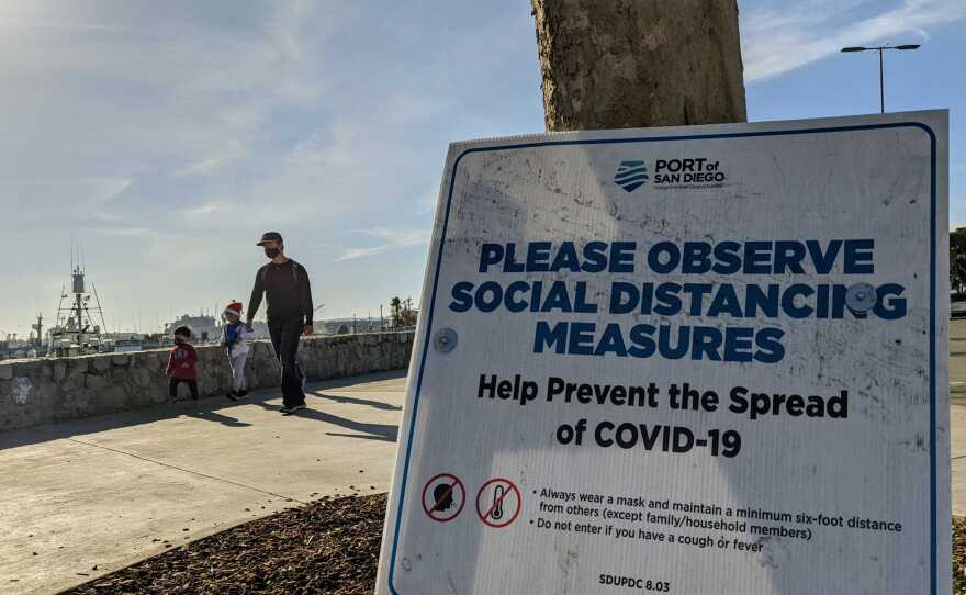 A sign reminding people of socially distance during the COVID-19 pandemic at Tuna Harbor Park at the Embarcadero in downtown San Diego on Dec. 13, 2020.