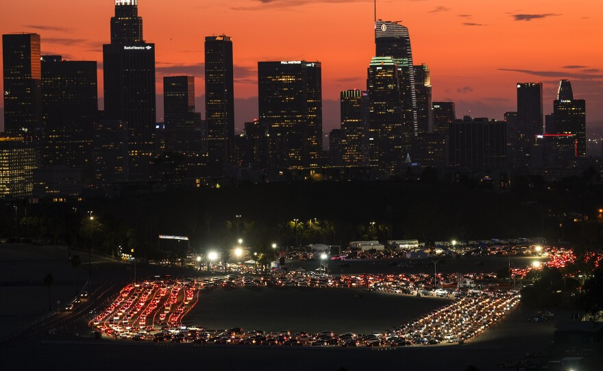 Motorists wait in lines to take a coronavirus test in a parking lot at Dodger Stadium, Monday, Jan. 4, 2021, in Los Angeles.