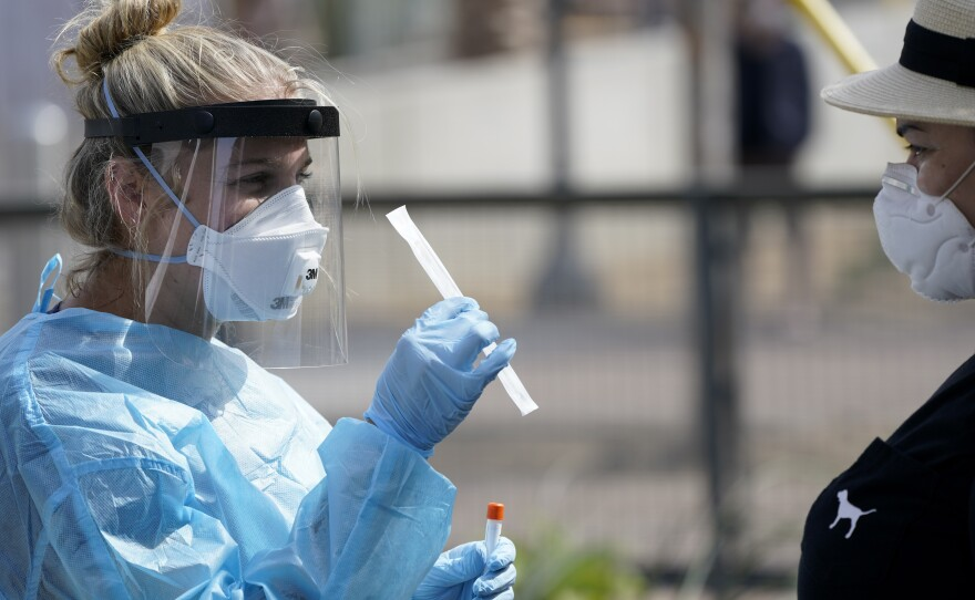 Nurse practitioner Debbi Hinderliter, left, collects a sample from a woman at a coronavirus testing site near the nation's busiest pedestrian border crossing in San Diego. Aug. 13, 2020