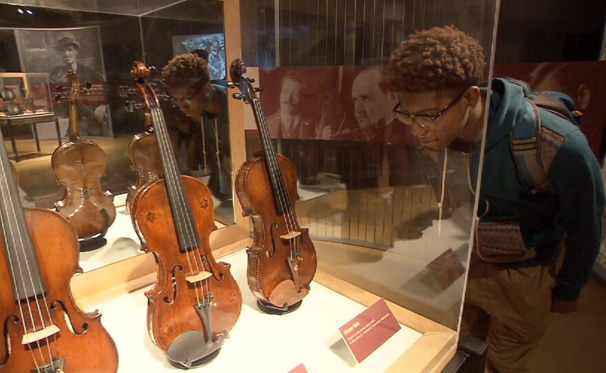 """A student visiting the """"Violins of Hope"""" exhibit at the Maltz Museum of Jewish Heritage in Ohio."""