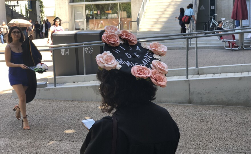 """A UC San Diego graduate wears a cap that reads """"Daughter of immigrants"""" in Spanish, June 15, 2018."""