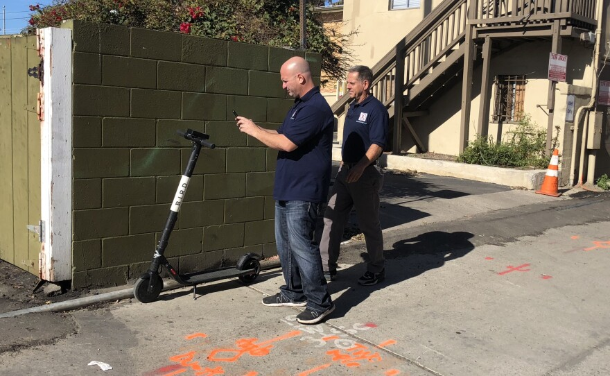 Dan Borelli (left) and John Heinkel (right) prepare to impound a dockless scooter left on private property in Pacific Beach, Jan. 24, 2019.