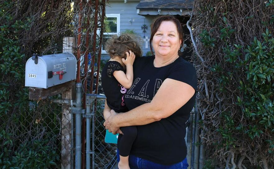 Katherine LeMoine stands outside her home holding her niece, Oct. 8, 2015.