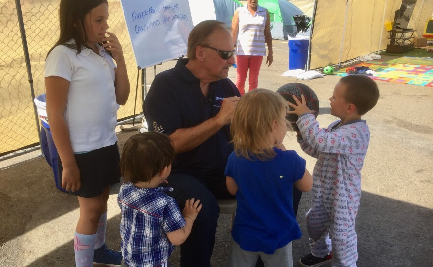 Bob McElroy, CEO of the Alpha Project, talks to children at the homeless transitional camp near downtown San Diego, Oct. 17, 2017.