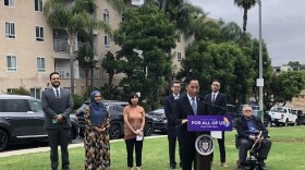 """Mayor Todd Gloria discusses his plans to seek additional funding for the city's rental and utility assistance program. He is standing behind a podium thats reads, """"A San Diego for All of Us."""" He is standing in front of a group of other people including, from left to right, Gilberto Vera, senior attorney, Legal Aid Society of San Diego, Nao Kabashima, executive director, Karen Organization of San Diego, City Council President pro Tem Stephen Whitburn,  District 3,  and City Councilmember Sean Elo-Rivera, District 9. They are standing on green grass. An apartment complex is visible in the background."""