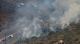 Smoke envelops a burning brush fire along state Route 67 near Slaughterhouse Canyon Road in Lakeside, June 30, 2015.
