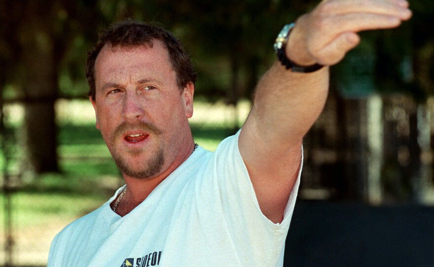 In this April 26, 1997, file photo, George Holliday points to the spot along a roadside in the Lake View Terrace section of Los Angeles where he videotaped Rodney King being beaten in April 1992, during a news conference in Los Angeles.