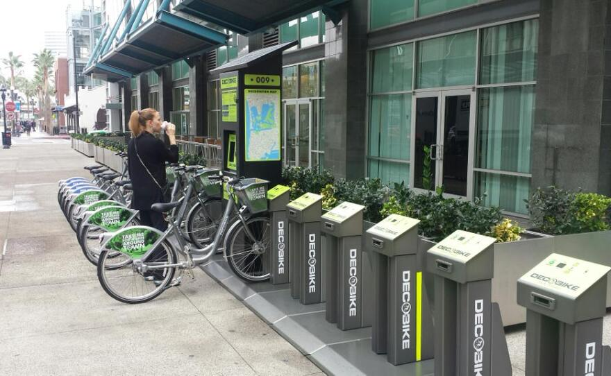A woman looks at an open DecoBike bike share station next to Petco Park in downtown San Diego on Friday, Jan. 30, 2015.