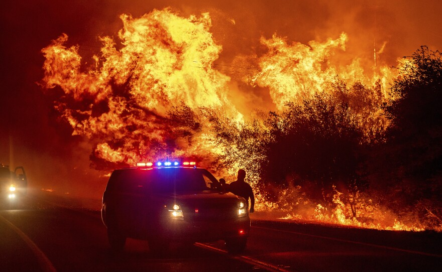 In this Sept. 9, 2020, file photo, flames lick above vehicles on Highway 162 as the Bear Fire burns in Oroville, Calif. Scientists say the outlook for the western U.S. fire season is grim because it's starting far drier than 2020's record-breaking fire year.