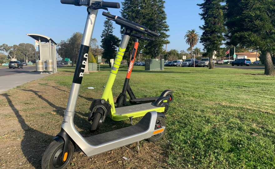 Bird, Link and Spin scooters are seen by an MTS bus stop in Mission Bay Park, March 30, 2021.