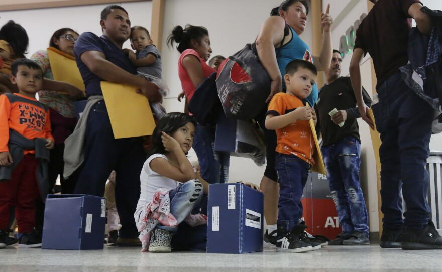 Immigrant families seeking asylum wait in line at the central bus station after they were processed and released by U.S. Customs and Border Protection, Friday, June 29, 2018.