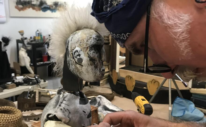 """Iain Gunn works on one of the puppets from """"The Society of Wonder."""""""