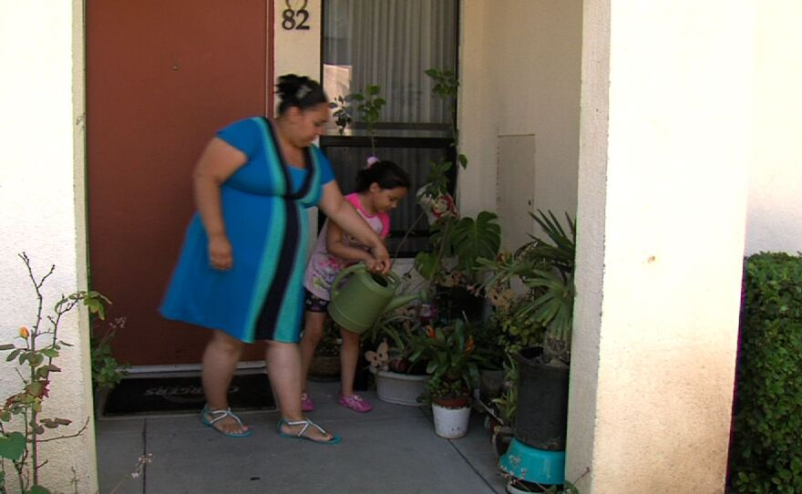 Clara Esparza waters flowers outside her Poway home with her daughter Isabella.