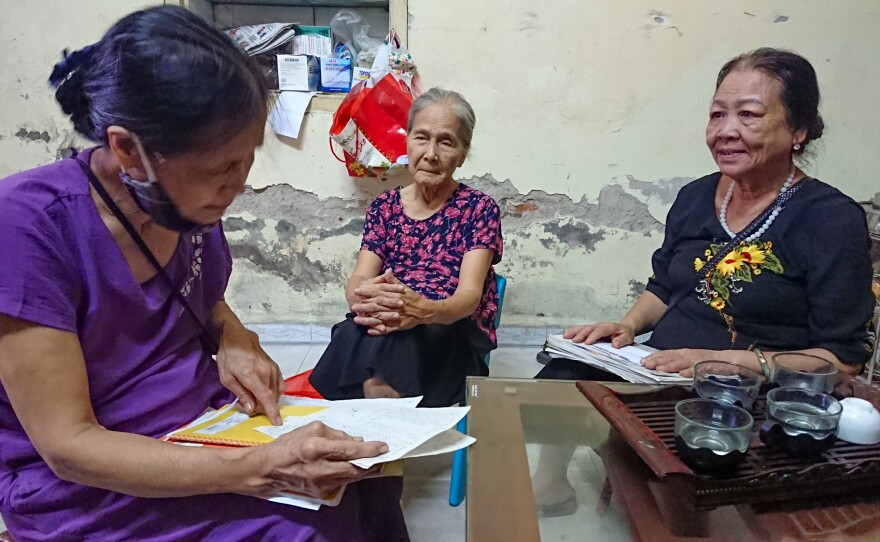 Dao Thi Hoa, chairwoman of the Intergenerational Self Help Club in the Khuong Din ward of Hanoi in Vietnam, checks the club's account book with other members.