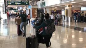 Airline passengers walk around San Diego International Airport with their luggage, Dec. 21, 2020.