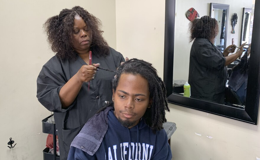 """Charlotte """"Peaches"""" Smith, owner of the Dreadlocks Salon, works on a customer's dreadlocks Wednesday, July 3, 2019, in Oakland, Calif. California has become the first state to ban workplace and school discrimination against black people for wearing hairstyles such as braids, twists and locks."""