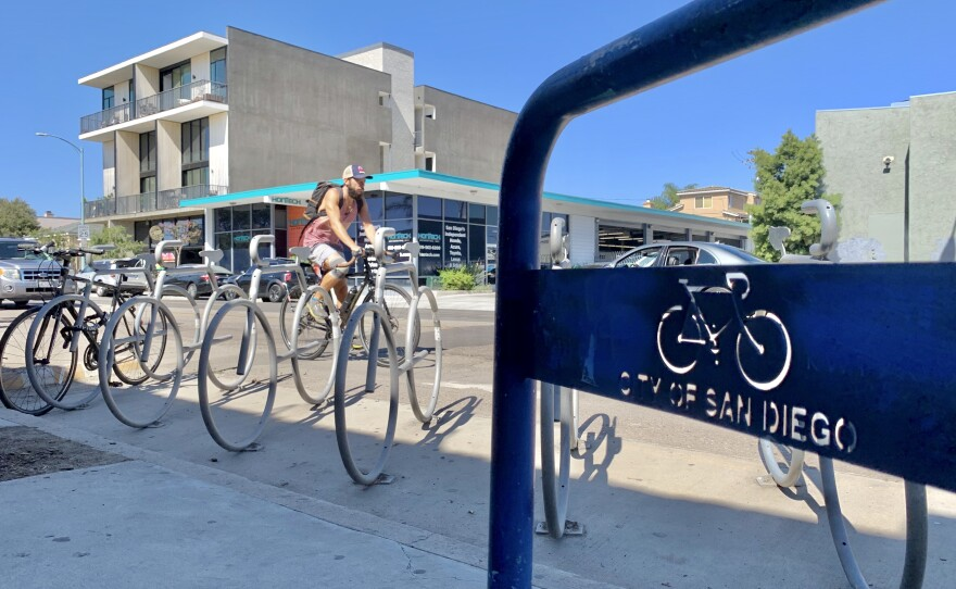 A cyclist rides past a bike corral on 30th Street in North Park, Aug. 6, 2020.