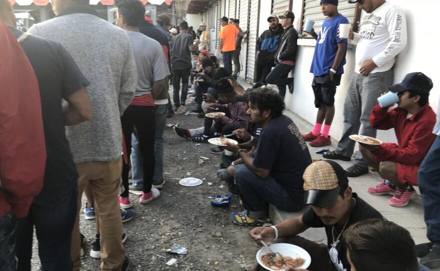 Migrants eat at El Barretal, Dec. 4, 2018.