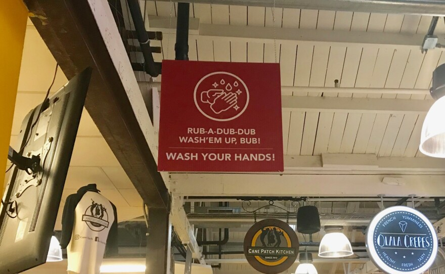 """A sign hanging from the ceiling reads """"Rub-a-dub-dub wash'em up, bub! Wash your hands!"""" at the Liberty Public Market food hall in Liberty Station. Sept. 19, 2020."""