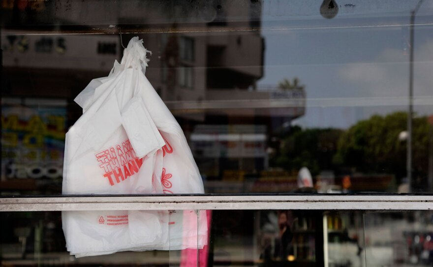 Plastic bags are seen through the window of a restaurant, May 24, 2012.