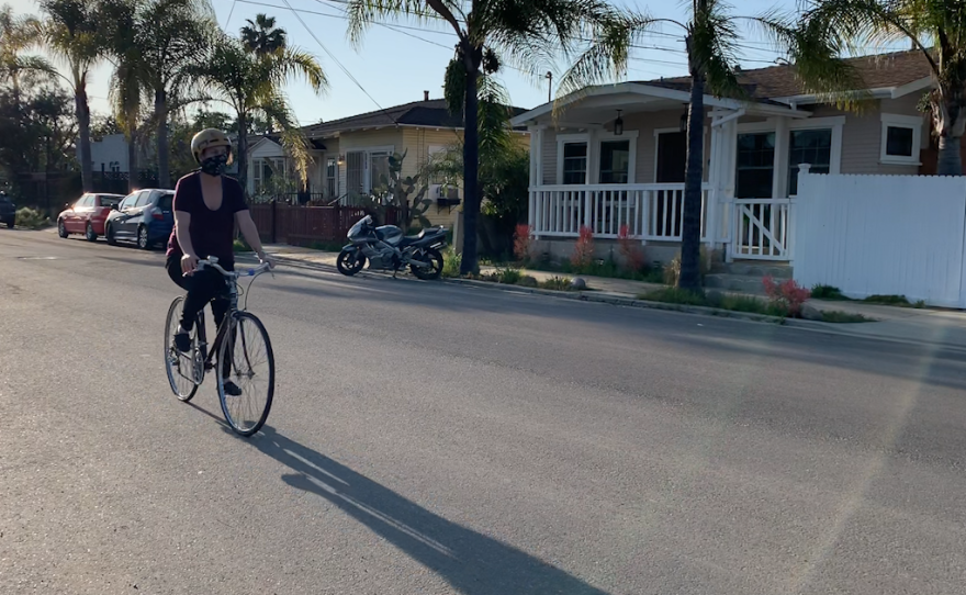 Ann King-Concialdi bikes through North Park while wearing a face covering, April 21, 2020.