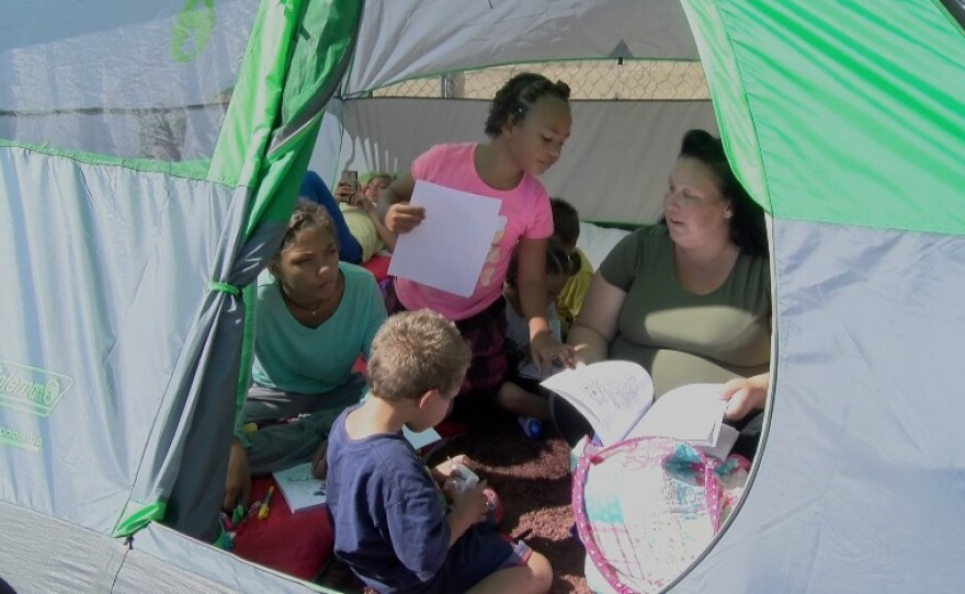 Christine Wade, 31, and her six children sit in their tent at the city of San Diego's transitional homeless camp near downtown, Oct. 12, 2017.
