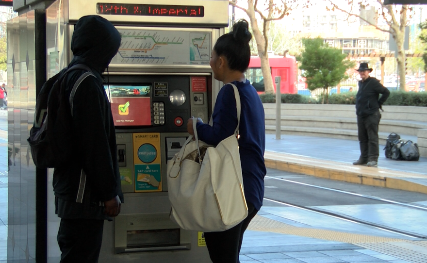 Two transit riders stand in front of a ticket vending machine at the 12th and Imperial trolley station, Dec. 26, 2017.
