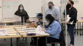 Observers look over the shoulders of election workers recounting ballots in the Santee City Council District 4 race, Dec. 14, 2020.
