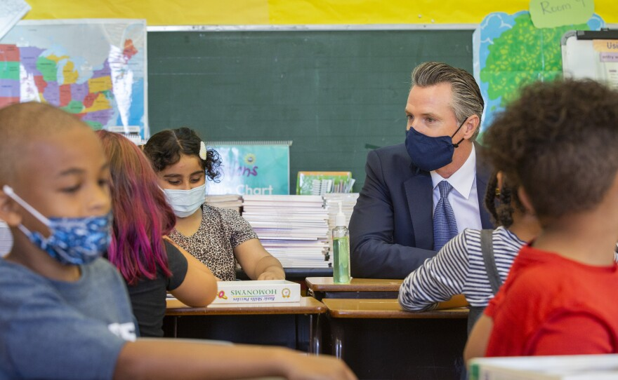 In this Aug. 11, 2021, file photo, California Gov. Gavin Newsom sits among students of a second-grade classroom at Carl B. Munck Elementary School, in Oakland, Calif.