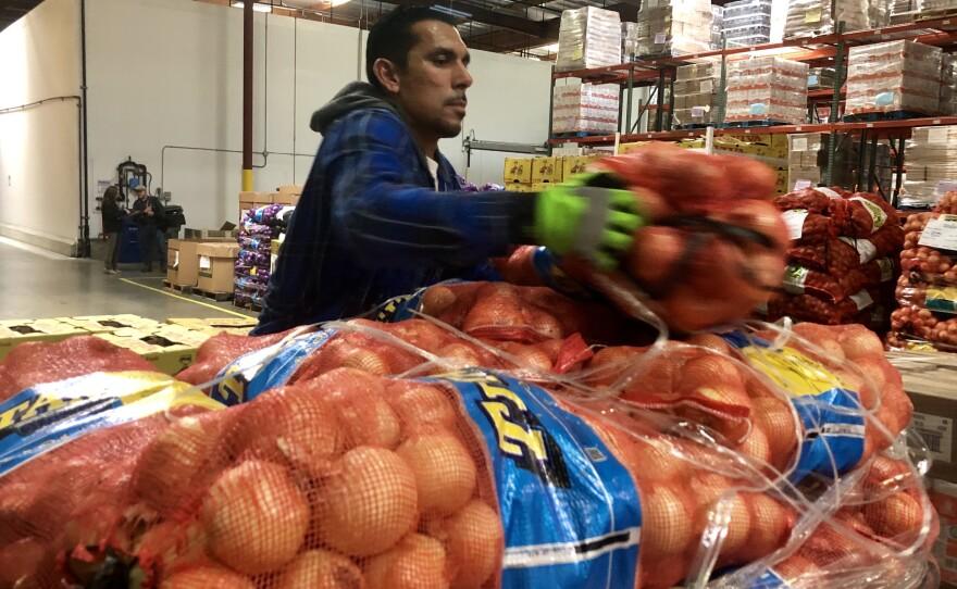A Feeding San Diego employee loads onions onto a pallet, March 17, 2020.