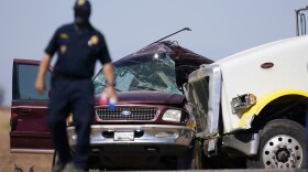 Law enforcement officers work at the scene of a deadly crash in Holtville, Calif., on Tuesday, March 2, 2021. Authorities say a semi-truck crashed into an SUV carrying multiple people on a Southern California highway, killing at least 13 people and injuring others.