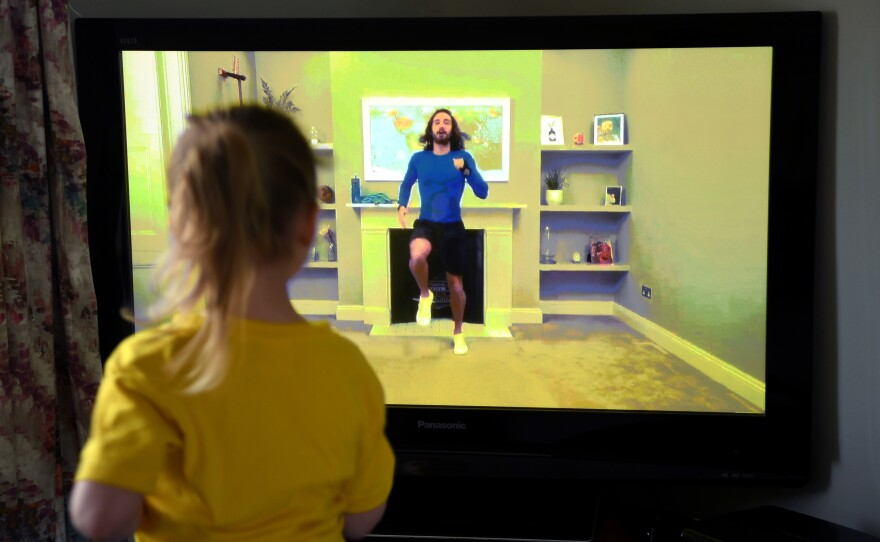 """Four-year-old Lois Copley-Jones, the photographer's daughter, takes part in a livestreamed broadcast of """"PE With Joe"""" on March 23, 2020, in Newcastle-under-Lyme, England. The popular fitness series ended Friday."""