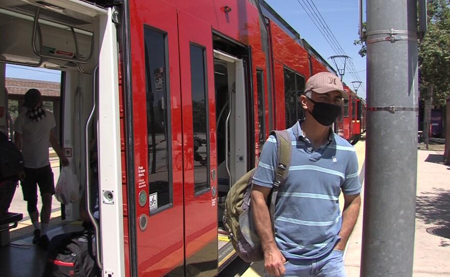 A man with a face covering exits an MTS trolley at the Old Town transit center, May 7, 2020.