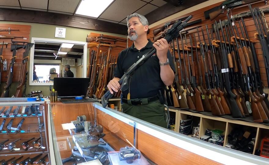 AO Sword Firearms owner David Chong displays a shotgun inside his El Cajon store, March 19, 2020.