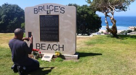 William Redmond III, a visitor from Atlanta, takes a photo of the historic plaque marking Bruce's Beach in April in Manhattan Beach, Calif.