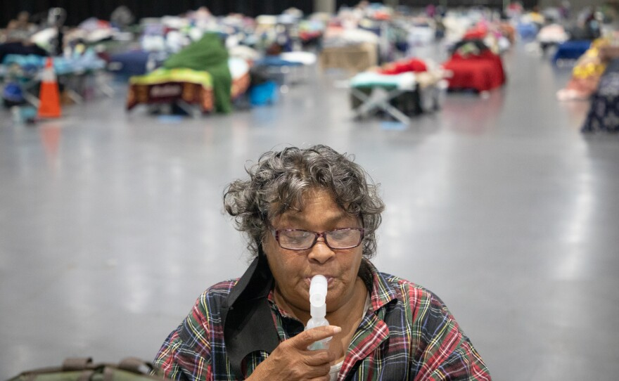 Deborah Jackson, who's been homeless for five years, uses a nebulizer to take albuterol for her asthma and COPD, May 21, 2020. Jackson has been staying in the Alpha Project section of the San Diego Convention Center since late April.