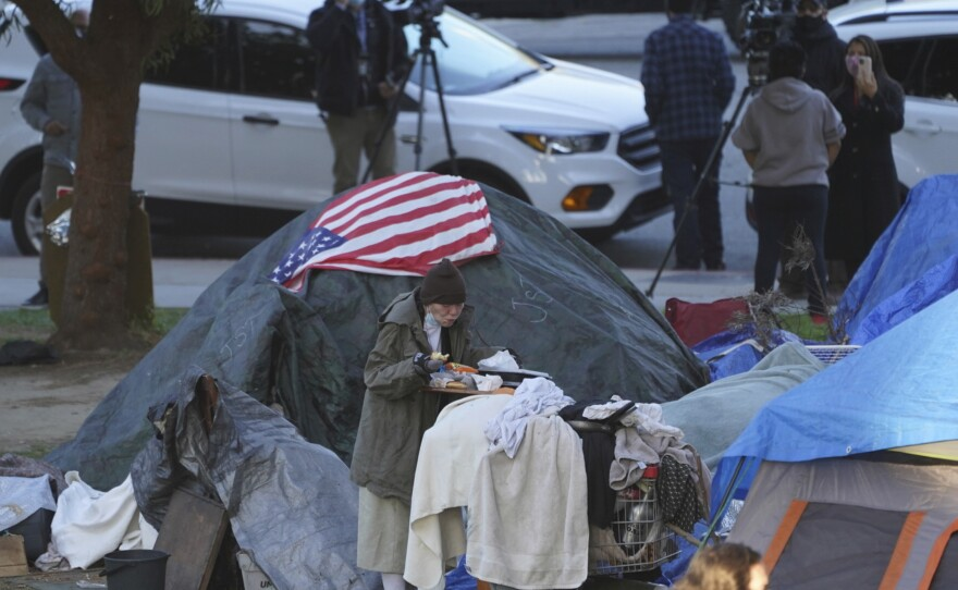 In this March 24, 2021, file photo a woman eats at her tent at the Echo Park homeless encampment at Echo Park Lake in Los Angeles.