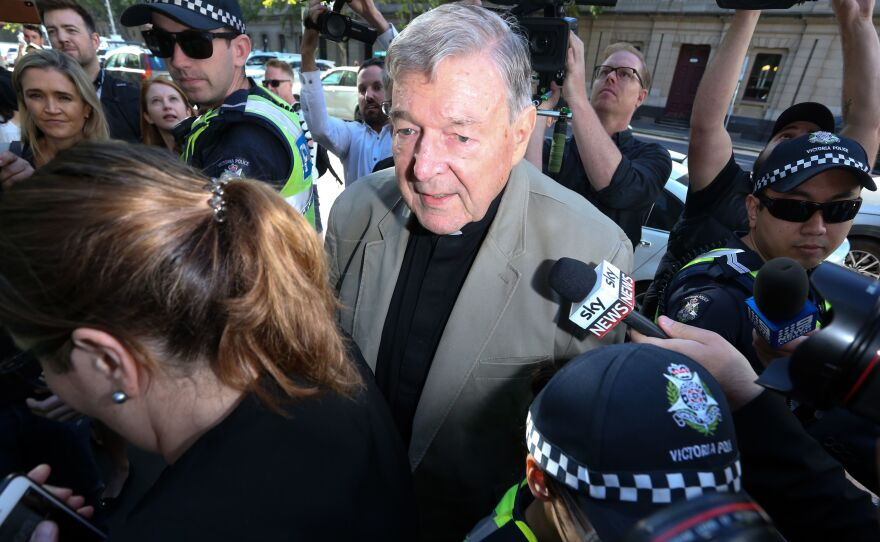 Cardinal George Pell makes his way through members of the media outside the court in Melbourne in February 2019. Australia's High Court has overturned his conviction on charges of child sexual abuse.
