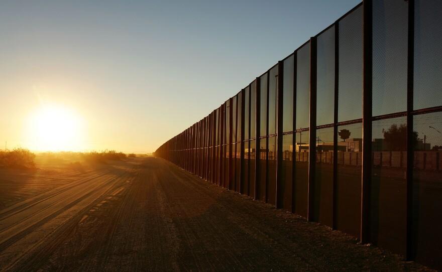 A metal fence runs along the U.S.-Mexico border east of San Luis, Ariz.