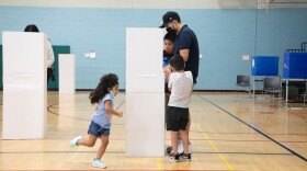 Hector and Maribel Hernandez fill out ballots with their three children at the Mid-City Gym in City Heights, Nov. 3, 2020.