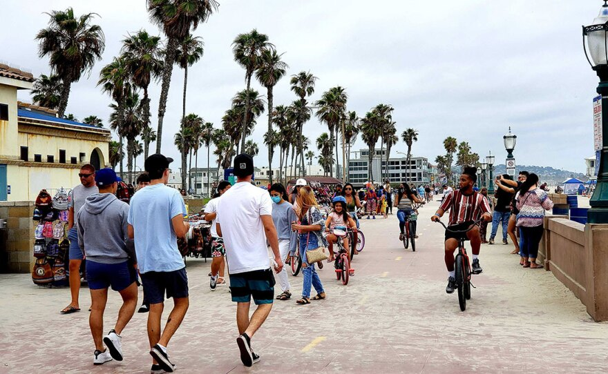 People on the Mission Beach boardwalk on June 24, 2020.