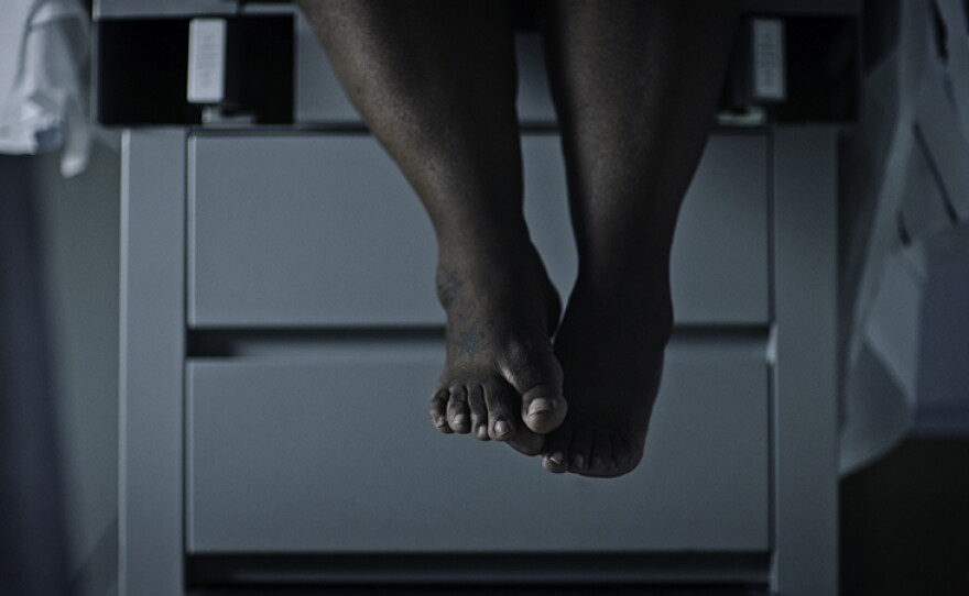 Woman's feet dangling off the edge of an exam table