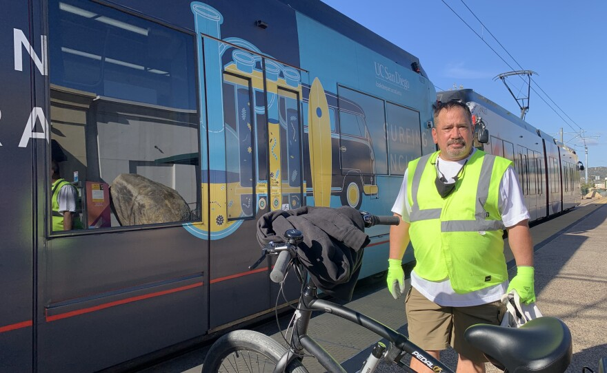 Roddy Jerome stands with his bicycle in front of a trolley car in Santee, March 4, 2021.