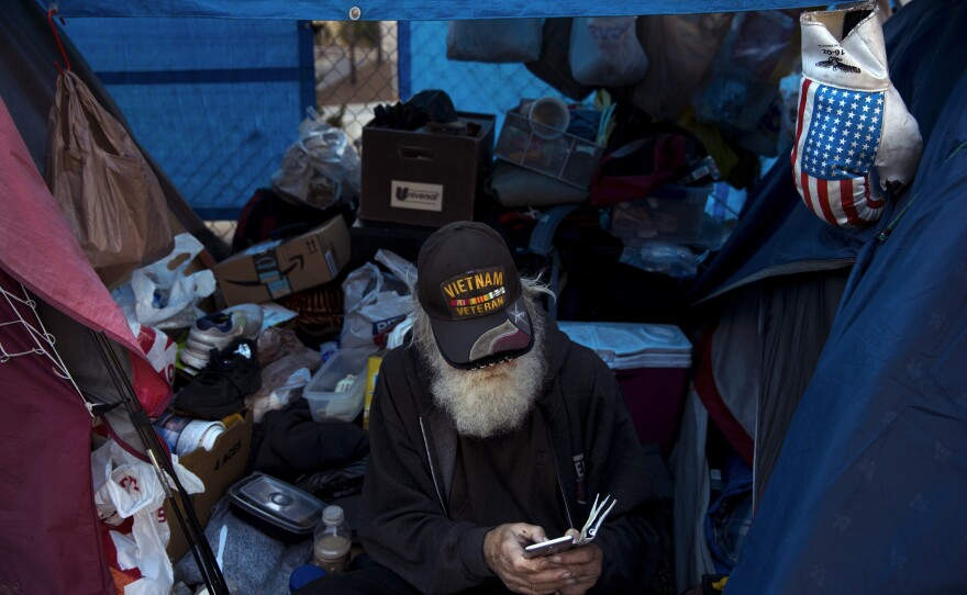 Theodore Neubauer, a 78-year-old Vietnam War veteran, who is homeless, looks at his smartphone while passing time in his tent in Los Angeles, Friday, Dec. 1, 2017.
